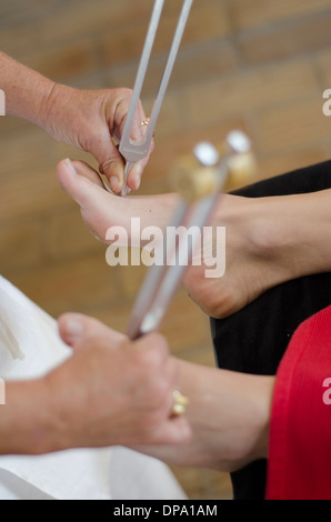 Close up of practitioner giving healing tuning fork treatment - Stock Image