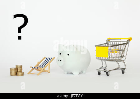 A question mark above a stack of coins, a deck chair, piggy bank and a shopping cart on white background, symbolic - Stock Image