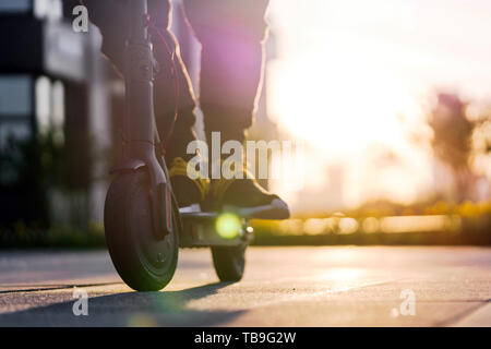 Close up of man riding black electric kick scooter at beautiful cityscape at sunset. Man is on foreground, modern building, business or commercial cen - Stock Image