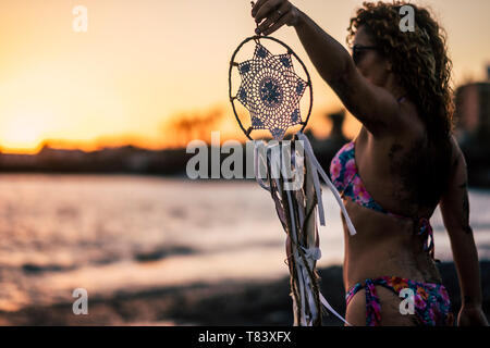 Beautiful people woman with bikini holding a white dreamcatcher outdoor at the beach enjoying sunset in a summer holiday vacation freedom feeling - Stock Image
