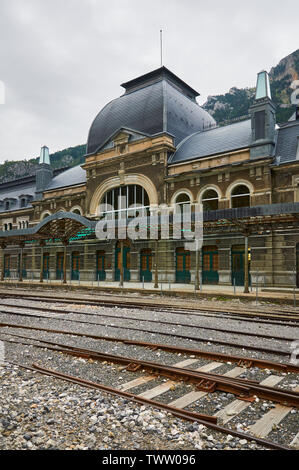 Frontage and entrance of the abandoned Canfranc International railway station and its railway tracks (Pyrenees, Jacetania, Huesca, Aragon, Spain) - Stock Image