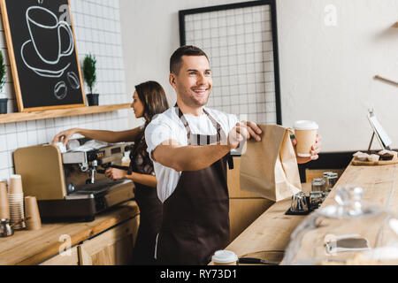 handsome cashier giving paper cup and bag wile barista making coffee behind bar counter in coffee house - Stock Image