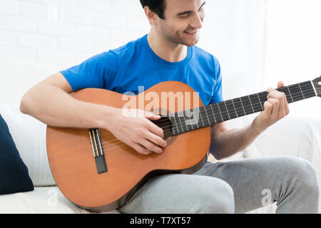 Handsome man playing on the guitar on the couch at home. Relaxed looking man sitting on a couch and playing the guitar. - Stock Image