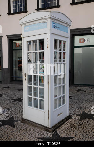 White telephone box is used as a library in São Miguel The Azores - Stock Image