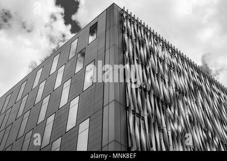 A black and white image looking up at a modern city office building against a cloudy sky in London - Stock Image