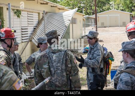 U.S. Airmen and Soldiers from the 3rd Chemical, Biological, Radiological, Nuclear Task Force, Pennsylvania National Guard, discuss aspects of their training scenario during the exercise Vigilant Guard, March 12, 2019, at Camp Santiago in Salinas, Puerto Rico. Members from the 3rd CBRN TF conducted wide-area search training, focusing on searching a large distance and going from building to building, marking and finding casualties. - Stock Image