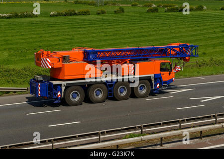 Mobile crane travelling on the M56 motorway in Cheshire UK - Stock Image