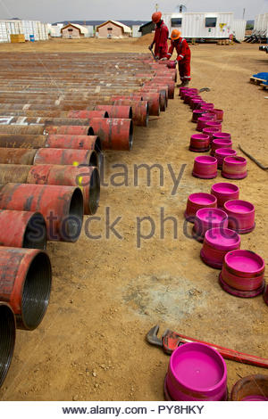 Workers by pipes with pink lids - Stock Image