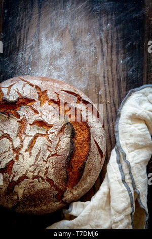Artisan sourdough bread with kitchen towel on floured wooden vintage board  with copy space - Stock Image