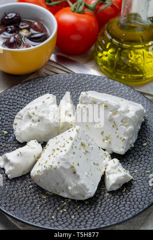 Fresh young soft white salted Feta cheese on black plate seasoned with dried oregano herb - Stock Image