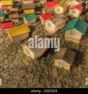 Miniature wooden houses with red, yellow, green and natural wood pattern roofs on grass lawn. - Stock Image
