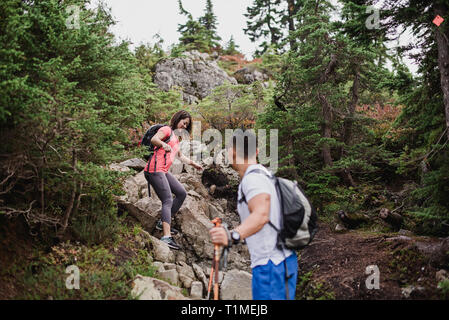 Couple hiking down rocks in woods - Stock Image