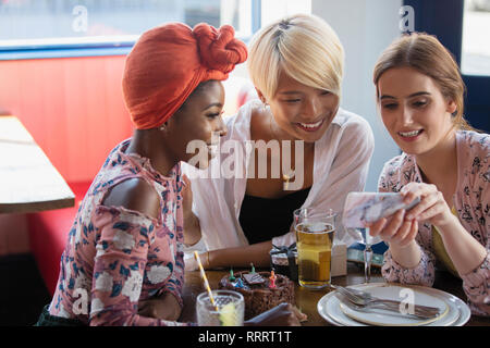 Young women friends using smart phone at restaurant table - Stock Image