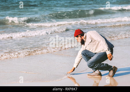 Man walking alone on sea beach summer travel vacations outdoor lifestyle weekend trip - Stock Image