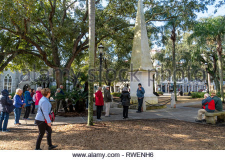 A tour group visits a monument at the Plaza de la Constitucion in the historic district of Saint Augustine, Florida USA - Stock Image