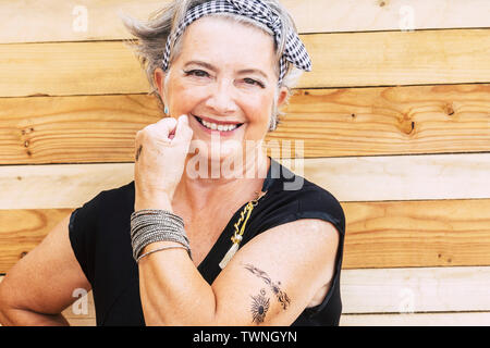 Rock and alternative cheerful senior caucasian woman show her tatoo on the arm smiilng at the camera - no limit age to have fun and enjoy lifestyle fo - Stock Image