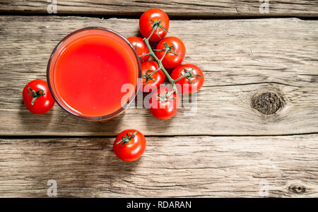 Tomato juice in the glass. On a wooden background. - Stock Image