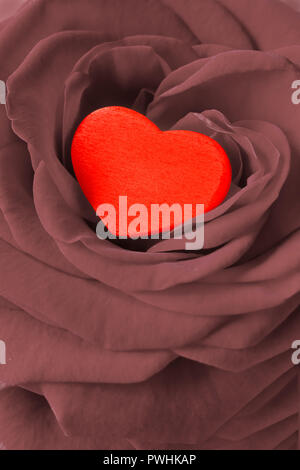 Red heart in a rose flower. Romantic background texture for a Valentine's or Wedding day greetings card, desaturated effect. - Stock Image