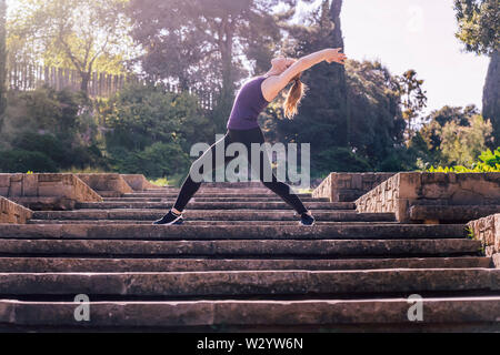 beautiful young woman doing yoga exercises on the stairs of the park, morning workout outdoors, sports and healthy lifestyle - Stock Image