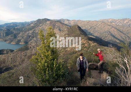 Two hikers navigate the Blue Ridge Loop overlooking Lake Berryessa. - Stock Image