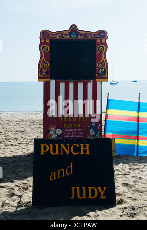 Red and White striped Punch and Judy booth ready for next show on the beach at Swanage - Stock Image