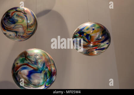 Three beautiful multi-colored glass blown balls hanging from the ceiling. - Stock Image