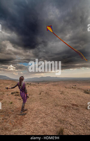 Maasai tribesman teaching a child to fly a kite. Kenya, Africa. - Stock Image
