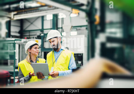 A portrait of a mature industrial man and woman engineer with tablet in a factory. Copy space. - Stock Image