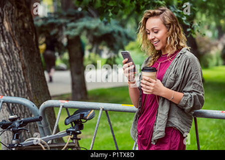 Portrait of a beautiful young female university student leaning on a bike rack on campus and reading texts on her smart phone - Stock Image