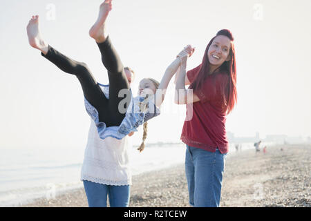 Playful lesbian couple swinging daughter on beach - Stock Image