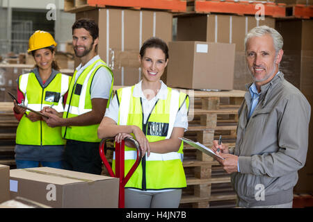 Portrait of warehouse manager and workers preparing a shipment - Stock Image