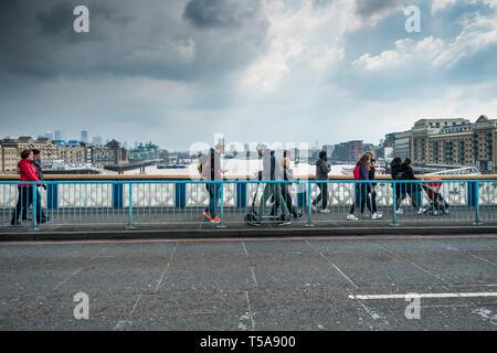 Pedestrians walking over Tower Bridge in London. - Stock Image