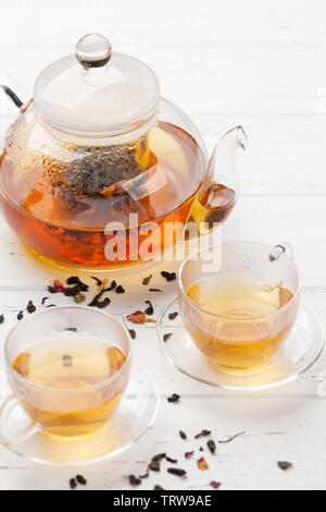 Herbal and fruit tea, teapot and cups on wooden table. With copy space - Stock Image