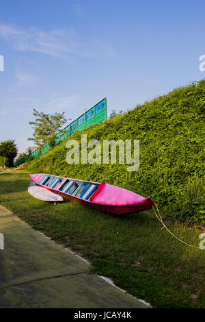 Red canoe laying on the green grass - Stock Image