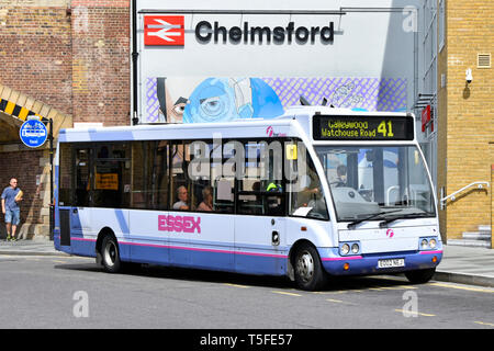 First Essex public transport single decker local passenger bus service & driver at bus stop outside Chelmsford train station entrance Essex England UK - Stock Image