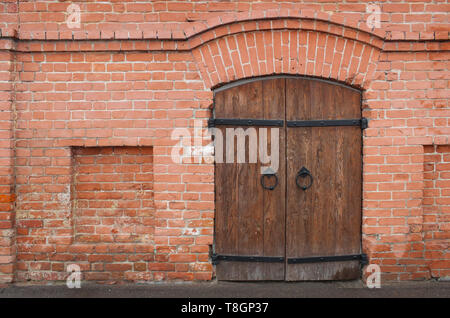 Old wooden gate in a red brick wall - Stock Image