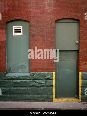 A green doorway and window on a red brick wall - Stock Image
