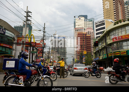 A policeman works a busy intersection in Makati City, Metro Manila, Philippines. - Stock Image