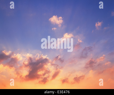 Sunset through clouds. - Stock Image