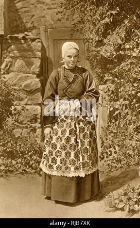 Breton woman in traditional costume at Douarnenez, Brittany, Northern France. She is wearing her Sunday best - during the week she works in the local sardine cannery. - Stock Image