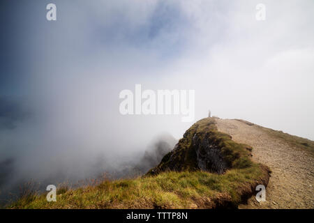 Scenic view of cliff surrounded by clouds - Stock Image