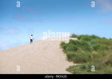 A young boy climbing up a sand dune at Crantock in Newquay in Cornwall. - Stock Image