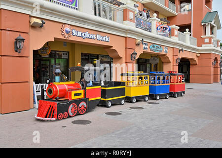 Small colorful children's train ride waiting for riders at the tourist resort of HarborWalk Village in Destin Florida USA. - Stock Image