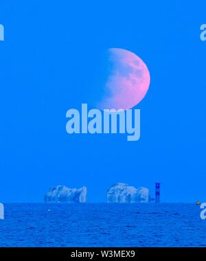 The Needles, Isle of Wight, UK.  16th July 2019. UK Weather.  The eclipsed full moon rises up above the Needles on the Isle of Wight on a clear calm evening.  Tonight's moon is in a partial eclispe and is due to be a maximum of 60% covered by the earths shadow at 10:30pm.  Picture Credit: Graham Hunt/Alamy Live News - Stock Image