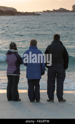 Three people looking out to sea waiting for the sunset - Stock Image