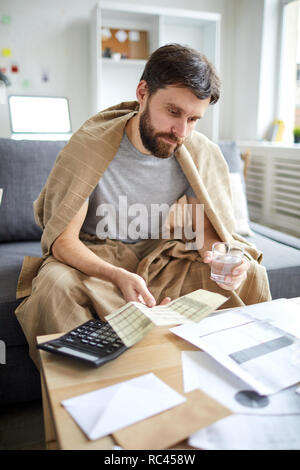 Pensive young man with glass of water comparing data on paper and payment bill while sitting on sofa by table - Stock Image