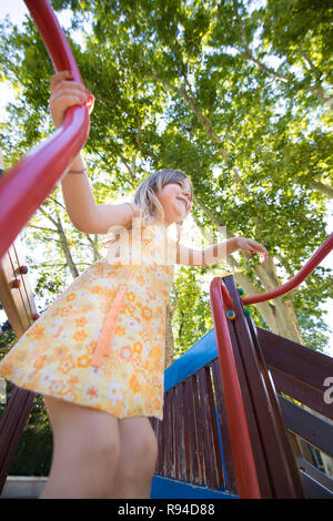low angle of three years old blonde girl with yellow dress playing  in outdoor playground, in public park with trees - Stock Image