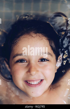 vertical portrait of a happy pretty little girl smiling lying in the tub while taking a bath in the bathtub, kids hygiene concept, copy space for text - Stock Image