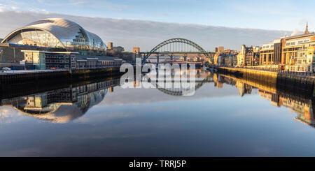 Newcastle, England, UK - February 5, 2019: Dawn light illuminates the Sage Gateshead, iconic Tyne Bridges and Newcastle Quayside on the River Tyne. - Stock Image