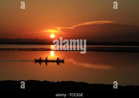 Silhouette of fisherman sailing on Limboto lake, Gorontalo, Indonesia - Stock Image